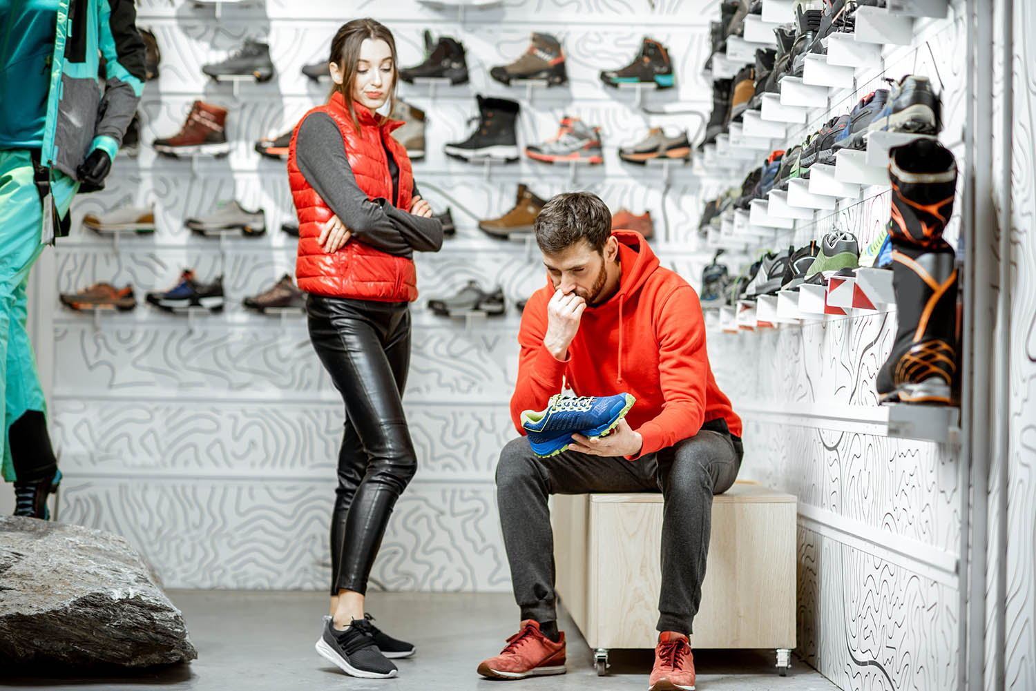 Adobe Stock - Man and woman choosing shoes for hiking sitting in the fitting room of the modern sports shop